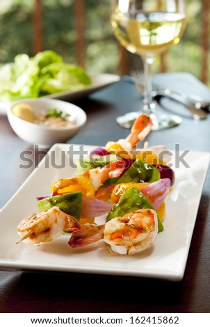 Closeup of grilled shrimp, avocado, red onion and yellow pepper kebabs in a restaurant setting. - stock photo