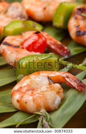 Closeup of grilled shrimps on rosemary sprigs over palm leaves. Tropical theme. - stock photo