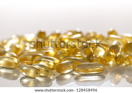 Closeup of group of coconut oil capsules. Shallow DOF. Focus on foreground. - stock photo