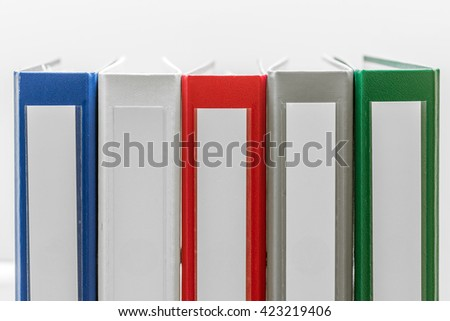 Closeup of group of colourful folders in a row in center of white background - stock photo