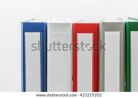 Closeup of group of colourful folders in a row on the right side of white background - stock photo
