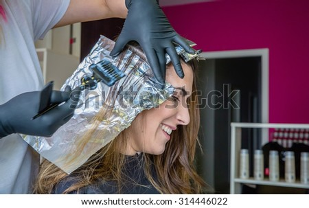 Closeup of hairdresser hands applying hair dye to happy young woman in a hair and beauty salon - stock photo