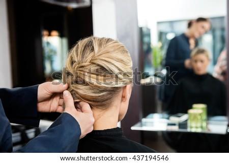 Closeup Of Hairdresser's Hands Braiding Client's Hair - stock photo