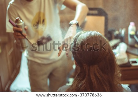 Closeup of hairdresser's hands using hairspray on client's hair at salon - stock photo