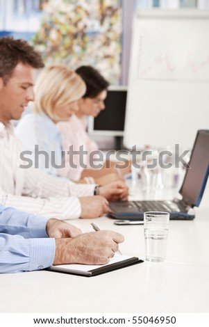 Closeup of hand, businessman writing notes on business meeting at office. Focus on hand. - stock photo