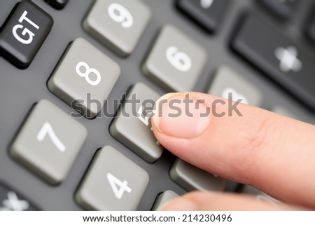 Closeup of hand calculating on a calculator. - stock photo