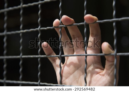 closeup of hand in jail - stock photo