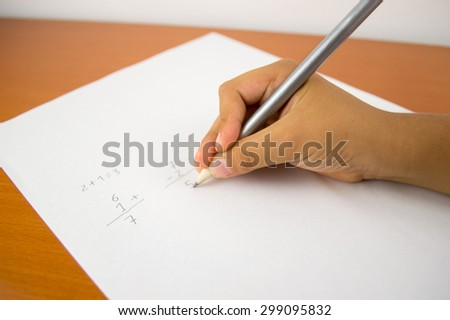 closeup of hand of a kid during the learning to make sums and substractions in the elementary school over the desk - stock photo