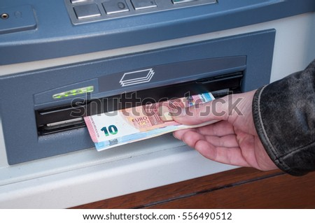 closeup of hand of man taking money at the automated machine of bank