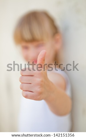 Closeup of hand of young girl doing thumbs up ok sign while leaning against concrete wall
