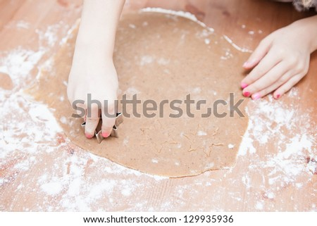 Closeup of hand of young girl making star shaped gingerbread biscuits with metal cutter from dough