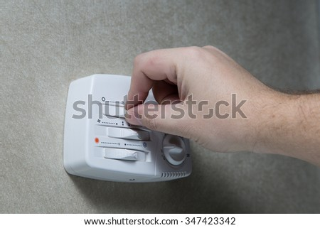 Closeup of hand setting a thermostat on the wall. Closeup shoot. - stock photo