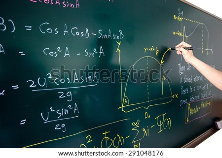 Closeup of hand writing complicated math equation on black board. - stock photo