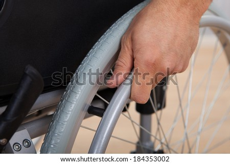 Closeup of handicapped man's hand pushing wheel of wheelchair - stock photo