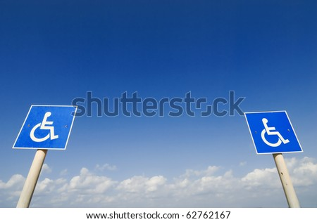 Closeup of handicapped parking place sign over blue sky