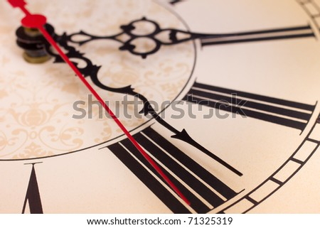 Closeup of hands and roman numerals on a clock - stock photo