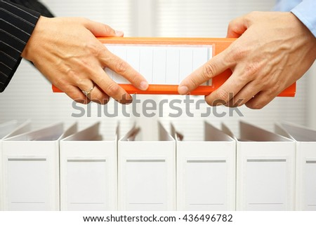 closeup of hands exchanging business documentation - stock photo
