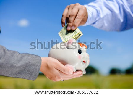 Closeup of hands holding a piggy bank with a dollar bills stuck in the top slot. Side view in horizontal format over a blue sky sunny outdoors background. - stock photo