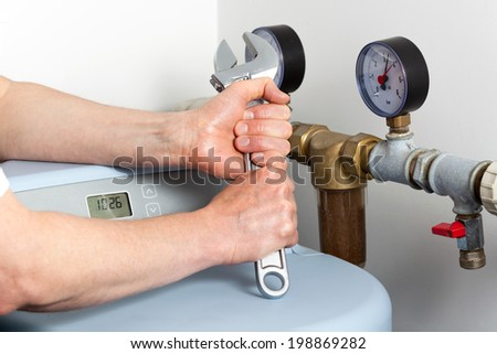 Closeup of hands holding wrench, boiler room - stock photo