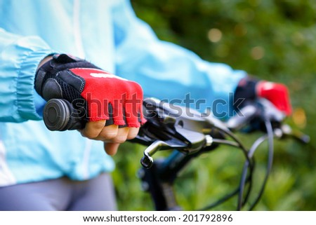 Closeup of hands in red protective gloves holding handlebar. - stock photo