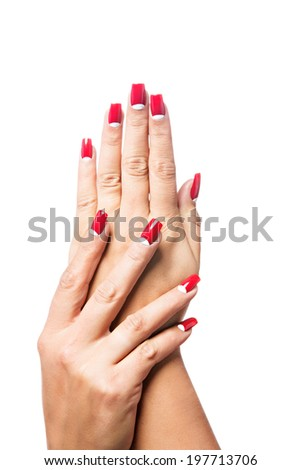 closeup of hands of a young woman with long red manicure on nails against white background - stock photo