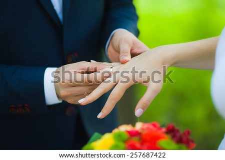 Closeup of hands of bridal unrecognizable couple with wedding rings. bride holds wedding bouquet of flowers. exchanging golden rings. love concept. family lifestyle. man woman. green background - stock photo