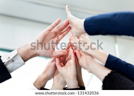 Closeup of hands of business people giving high-five - stock photo