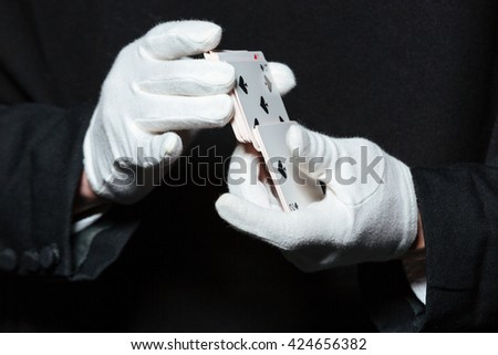 Closeup of hands of man magician in white gloves shuffling playing cards over black background - stock photo