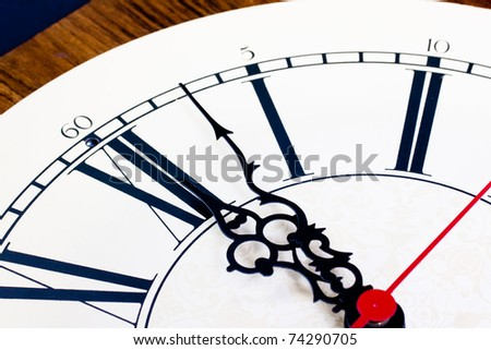 Closeup of hands on a clock just past 12:00 - stock photo