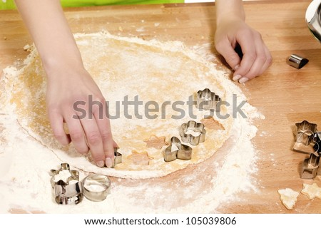 closeup of hands pressing christmas molds in dough on a kitchen table - stock photo