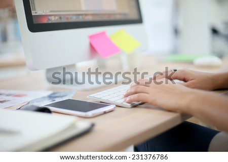 Closeup of hands typing on desktop keyboard - stock photo