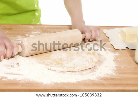 closeup of hands using rolling pin on dough - stock photo
