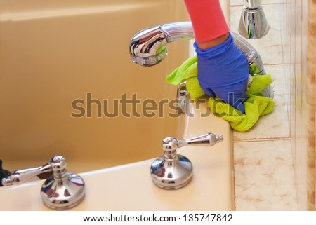 closeup of hands with purple latex gloves cleaning  bathroom with green microfiber cloth - stock photo