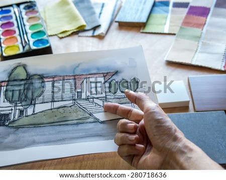 Closeup of hands working with architecture hand-drawn illustration/ material sample on wooden table top