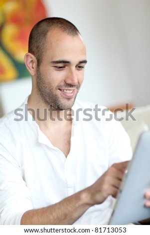 Closeup of handsome man websurfing on touchpad - stock photo