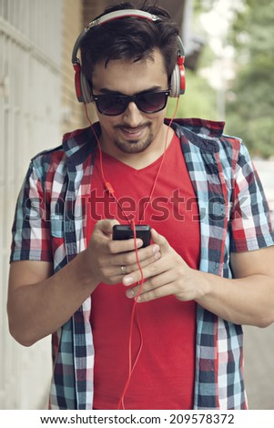 Closeup Of Handsome Young Man With Headphones Listening To Music Outdoors