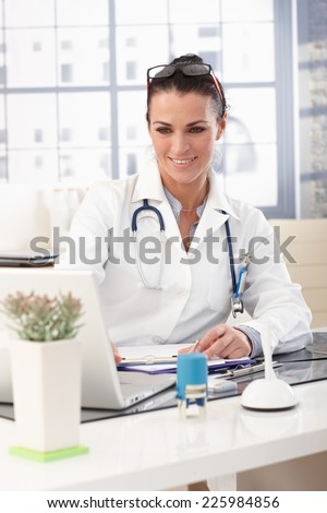 Closeup of happy brunette doctor working on laptop computer at medical office, wearing glasses, stethoscope and lab coat, smiling. - stock photo