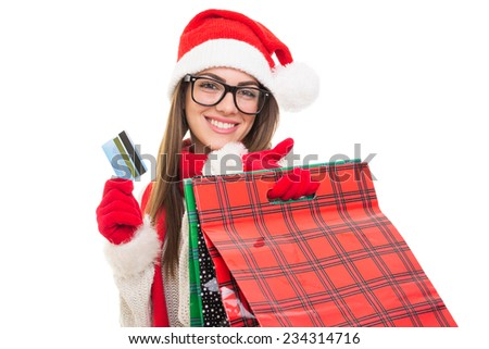Closeup of happy Christmas young woman with shopping bags and credit card smiling wearing eyeglasses and Santa Claus hat. Isolated on white background. - stock photo