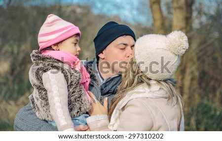 Closeup of happy couple with her little daughter kissing over a forest background. Family love concept. - stock photo