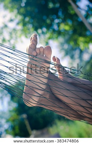 Closeup of happy family lying on hammock on sunny countryside background. Picture of man and children legs barefoot.  - stock photo