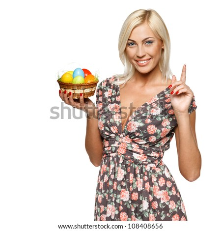 Closeup of happy female holding basket with Easter eggs with her finger up, isolated on white background