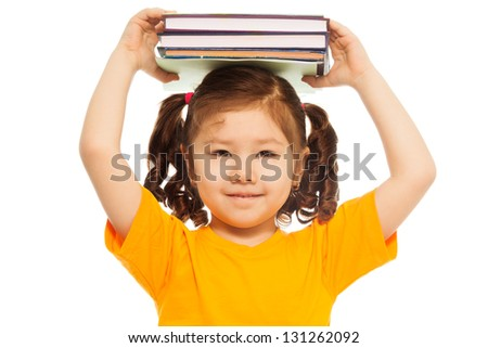 Closeup of happy little Asian girl with ponytails holding pile of books on top of her head  and smile, standing isolated on white - stock photo