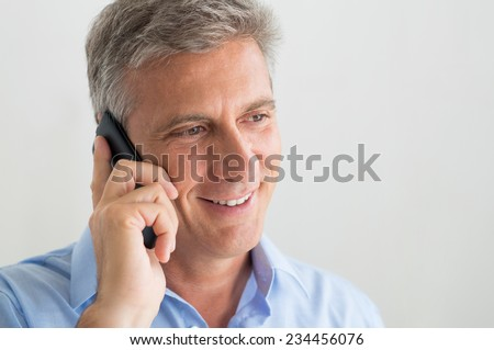 Closeup Of Happy Mature Businessman Listens On The Phone - stock photo