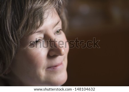 Closeup of happy middle aged woman looking away - stock photo