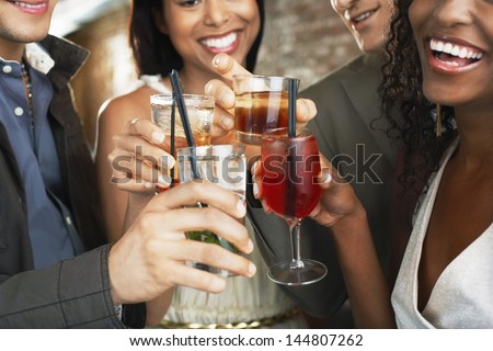 Closeup of happy multiethnic couples toasting drinks at the bar - stock photo