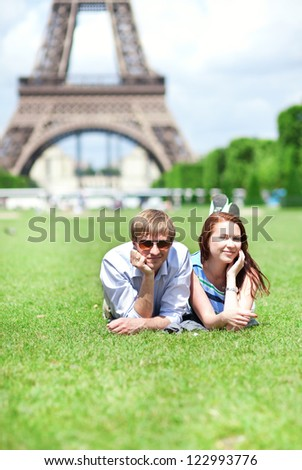 Closeup of happy positive couple laying on the grass near the Eiffel tower - stock photo