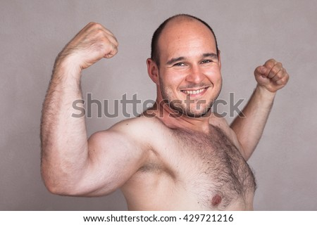 Closeup of happy shirtless man showing his strong arms and muscles.