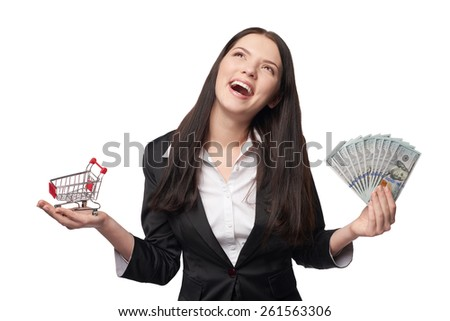 Closeup of happy woman with us dollar money in one hand and small empty shopping cart in other hand looking up in excitement, isolated on white background - stock photo