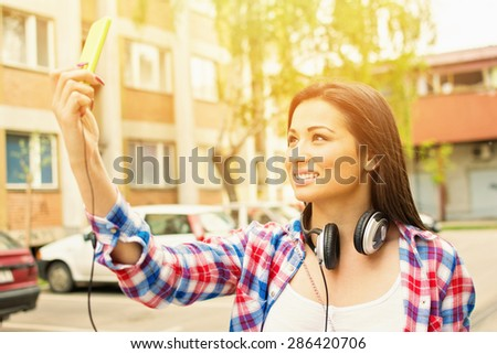 Closeup of happy young brunette woman with headphones taking a selfie with smartphone. Teenage girl in blue and red checkered shirt taking a self portrait with cellphone outdoors in urban environment. - stock photo