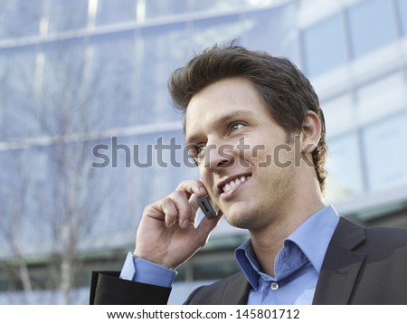 Closeup of happy young businessman using cell phone outside office building - stock photo